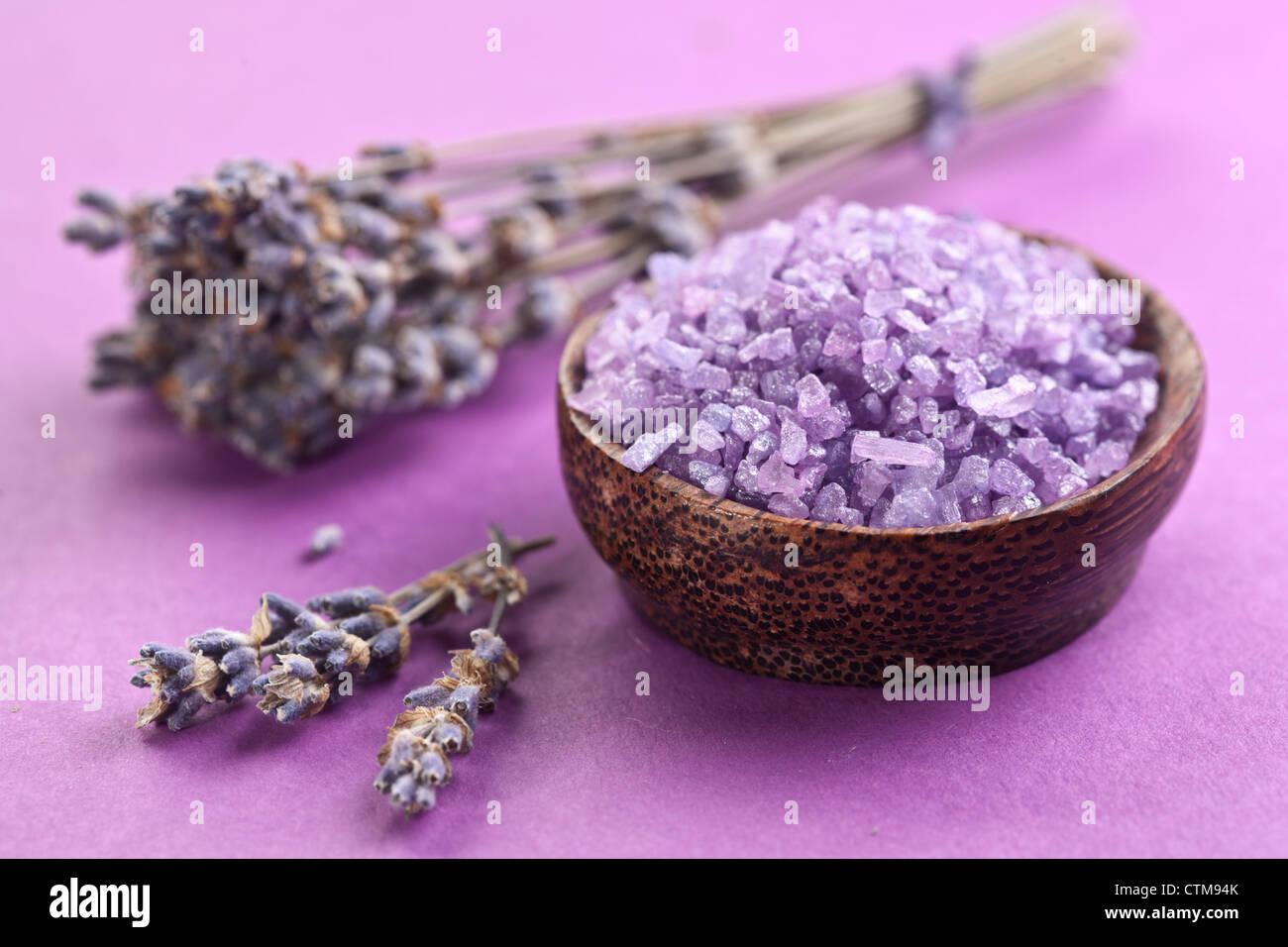Sal de mar y lavanda seca sobre un fondo violeta. Imagen De Stock