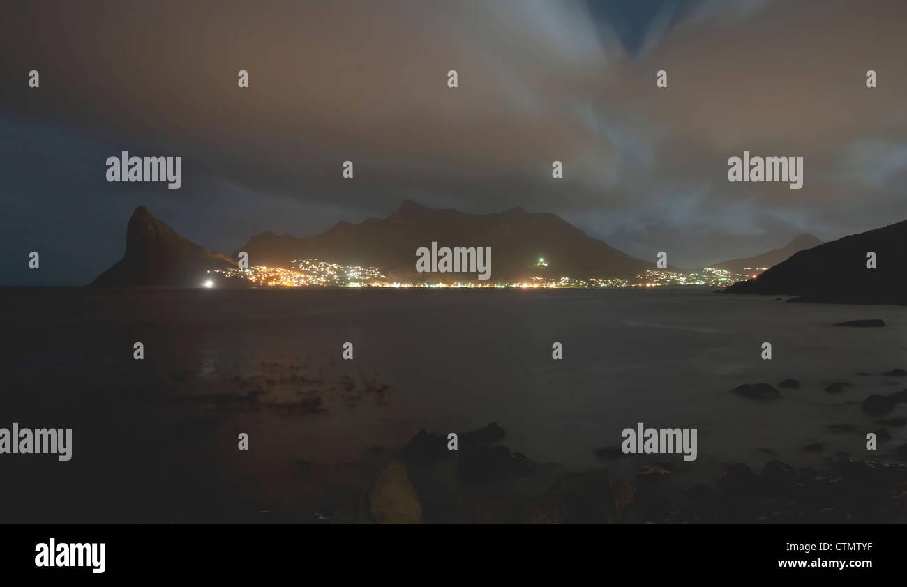 Hout Bay Harbour y centinela visto desde Tintswalo Atlantic lodge por la noche, en Ciudad del Cabo, Sudáfrica Foto de stock