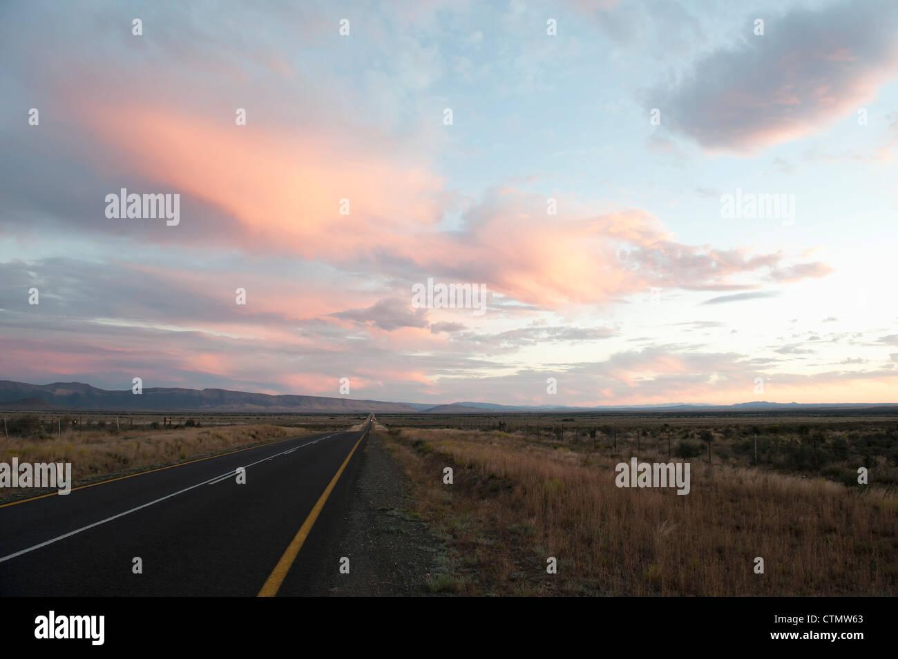 El largo camino: Los viajeros que llegan al atardecer en el Gran Karoo, Sudáfrica Foto de stock