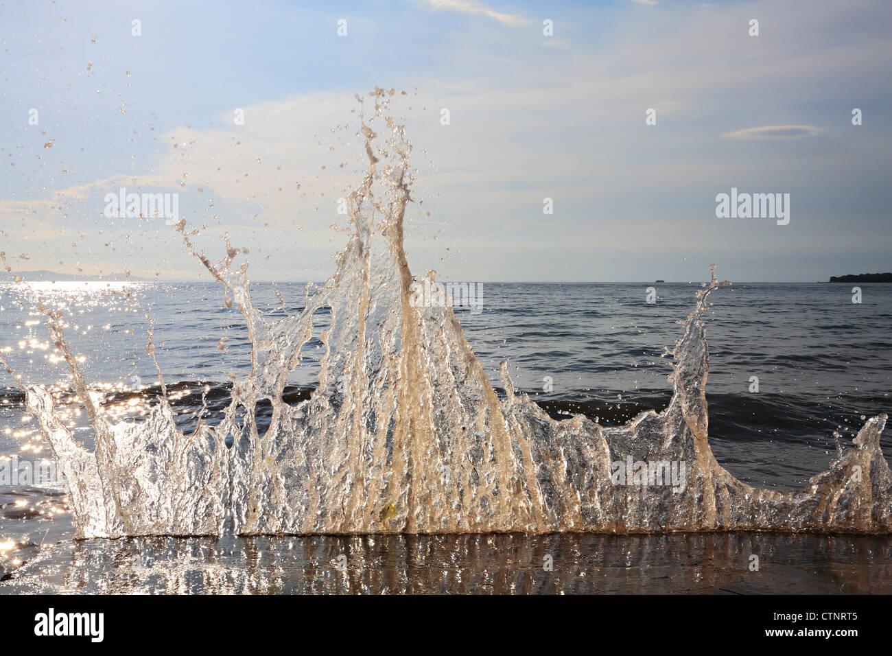 Salpicaduras de agua de mar en el rompeolas. Imagen De Stock