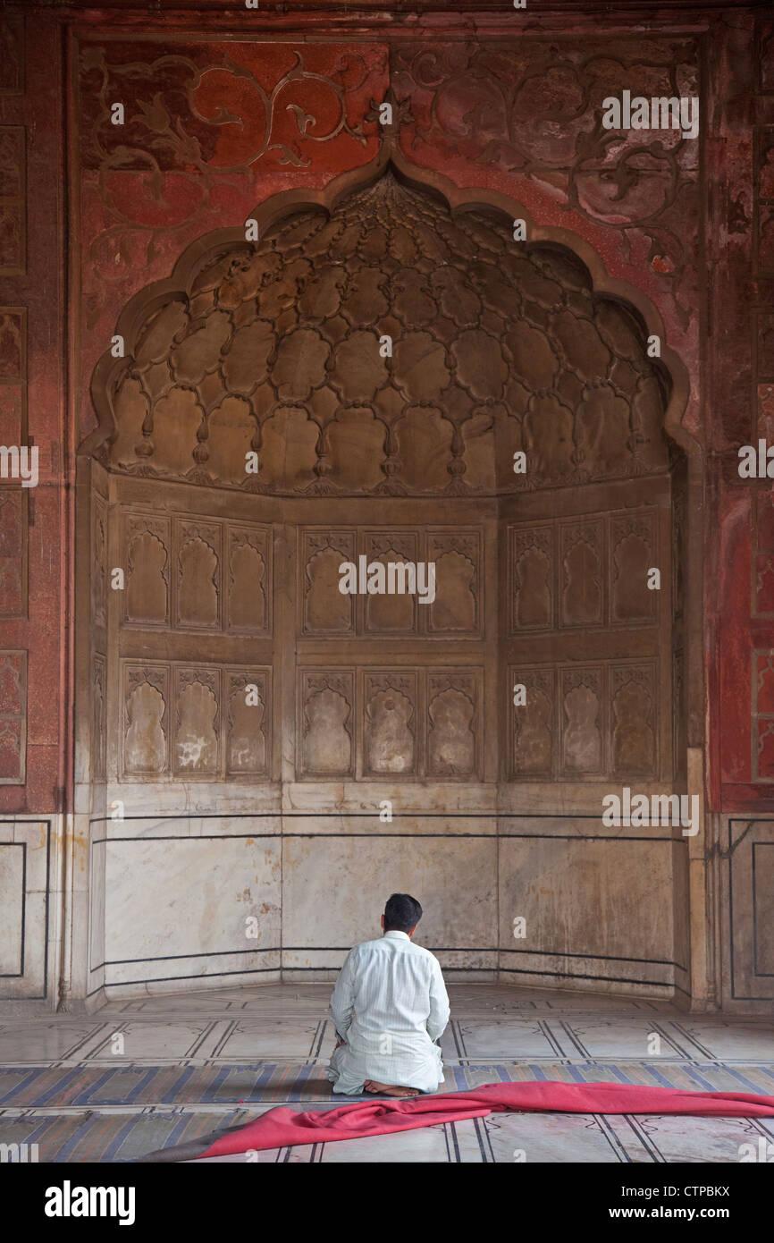 Rezar la oración musulmana en el área dentro de la Masjid-i Jahān-Numā / Jama Masjid mezquita en vieja Delhi, India Foto de stock