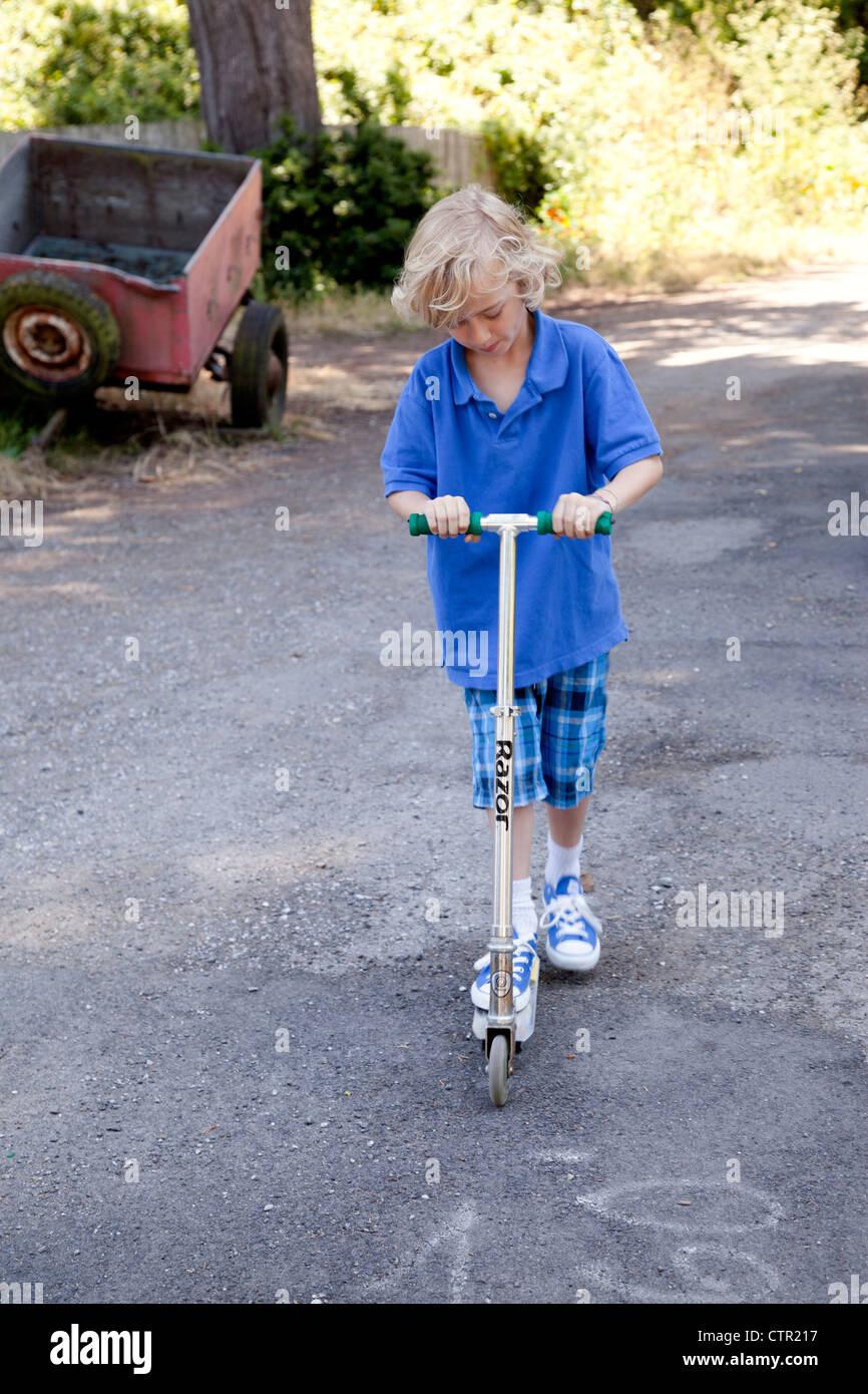 Niño jugando afuera en su scooter. Imagen De Stock