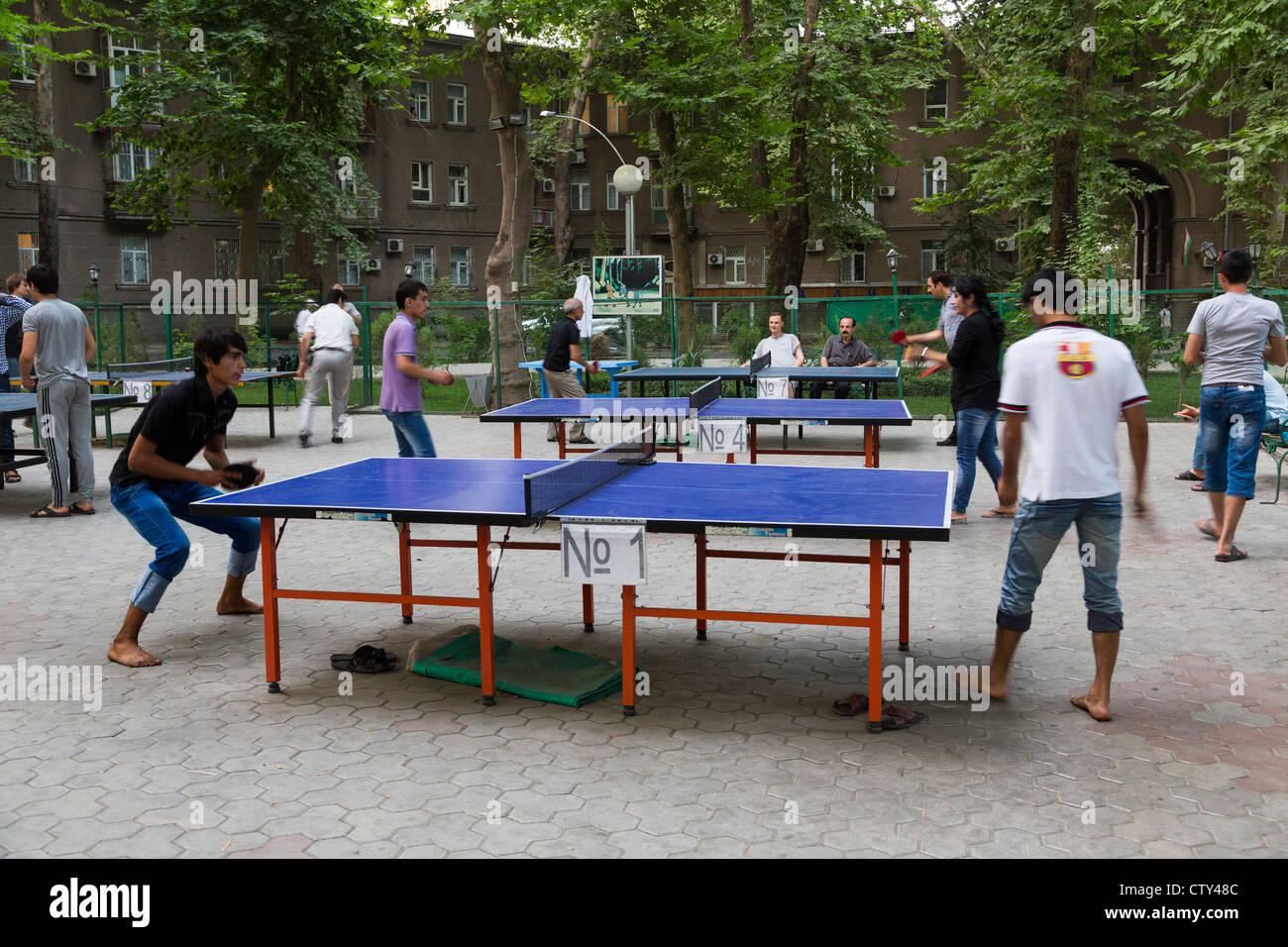 Jóvenes jugando al tenis de mesa en mesas al aire libre en Dushanbe, Tayikistán Imagen De Stock