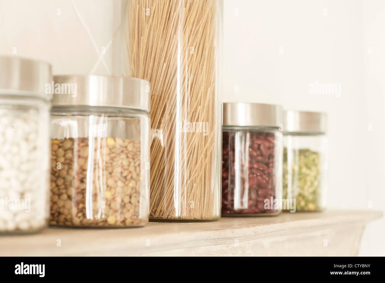 Pasta, lentejas y frijoles en frascos en la estantería. Imagen De Stock
