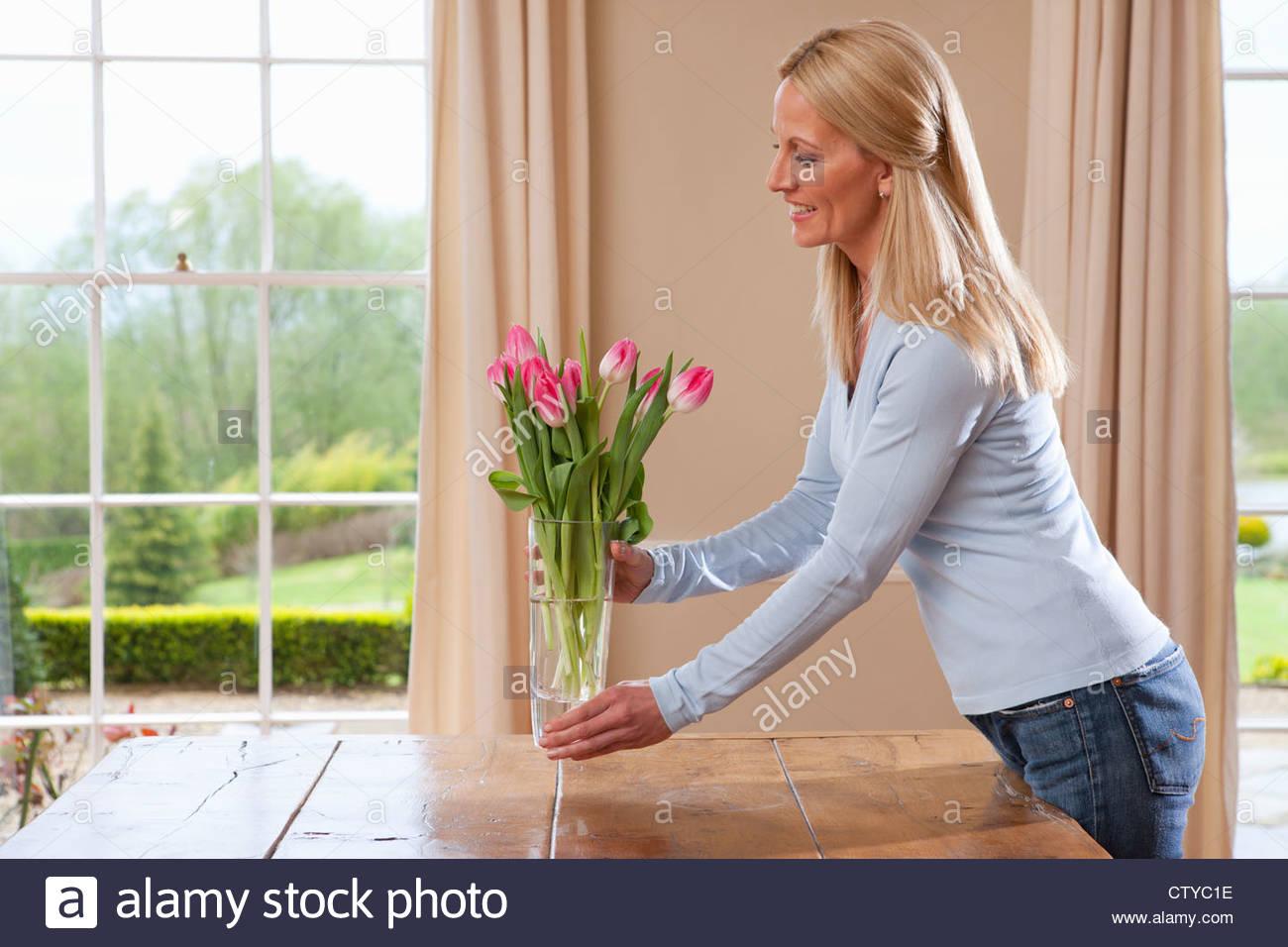 Mujer sonriente colocando jarrón con tulipanes en la mesa de comedor Imagen De Stock
