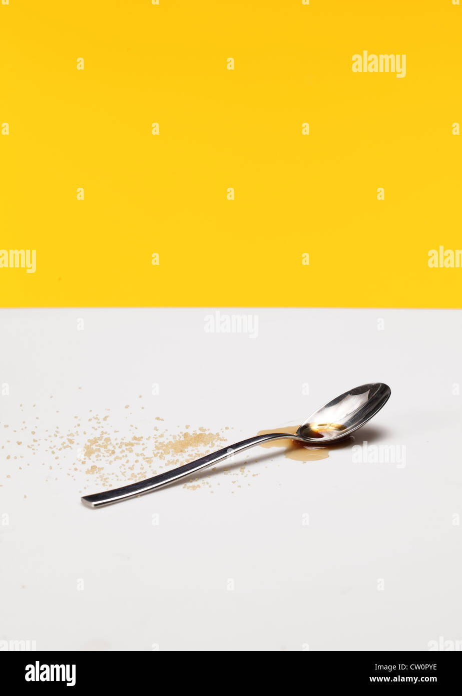 Una cuchara de café con café líquido, charco y espolvorea de azúcar Foto de stock