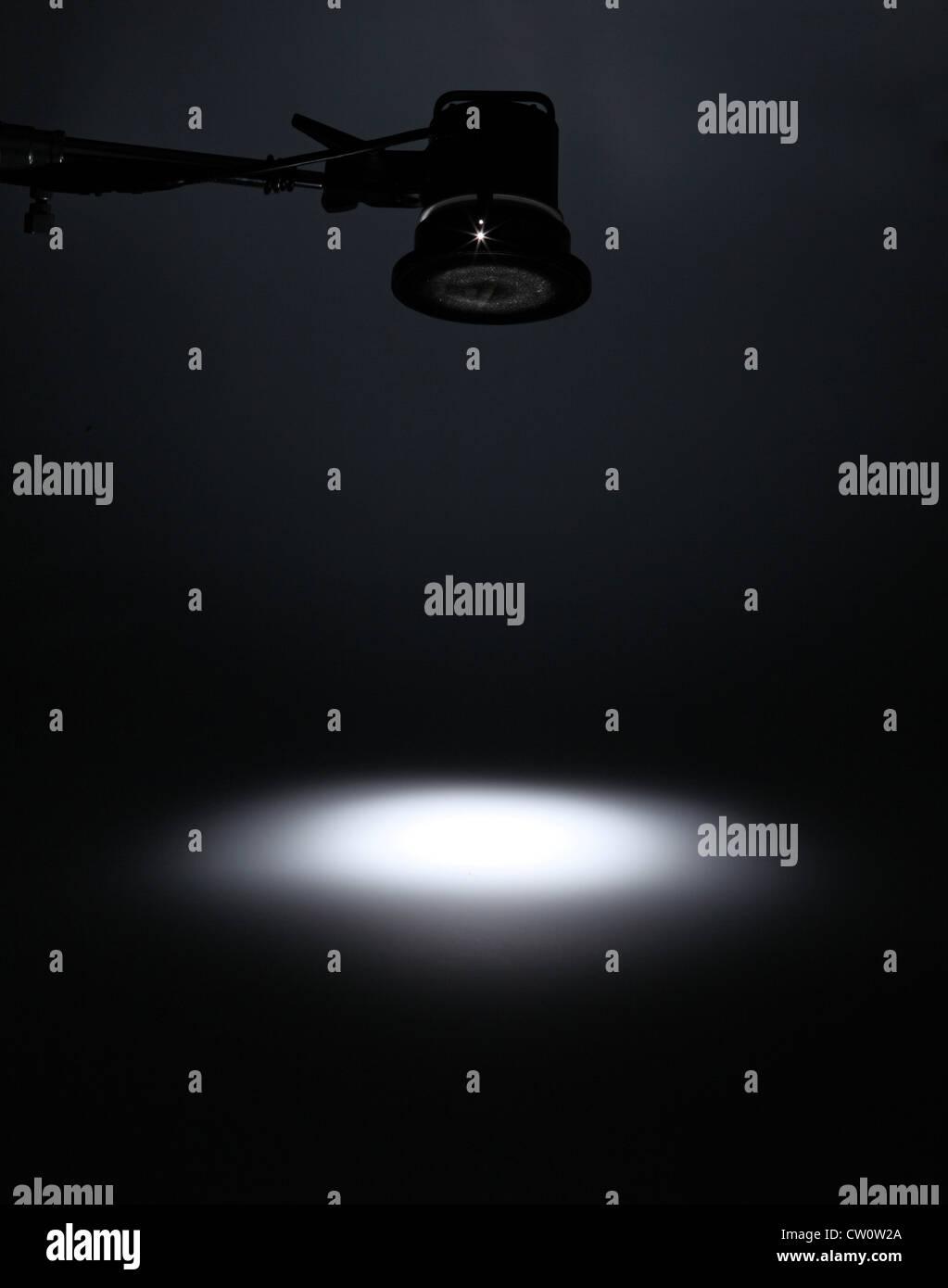 Una fotografía de luz por encima de la creación de un foco blanco sobre un fondo oscuro vacío. Imagen De Stock