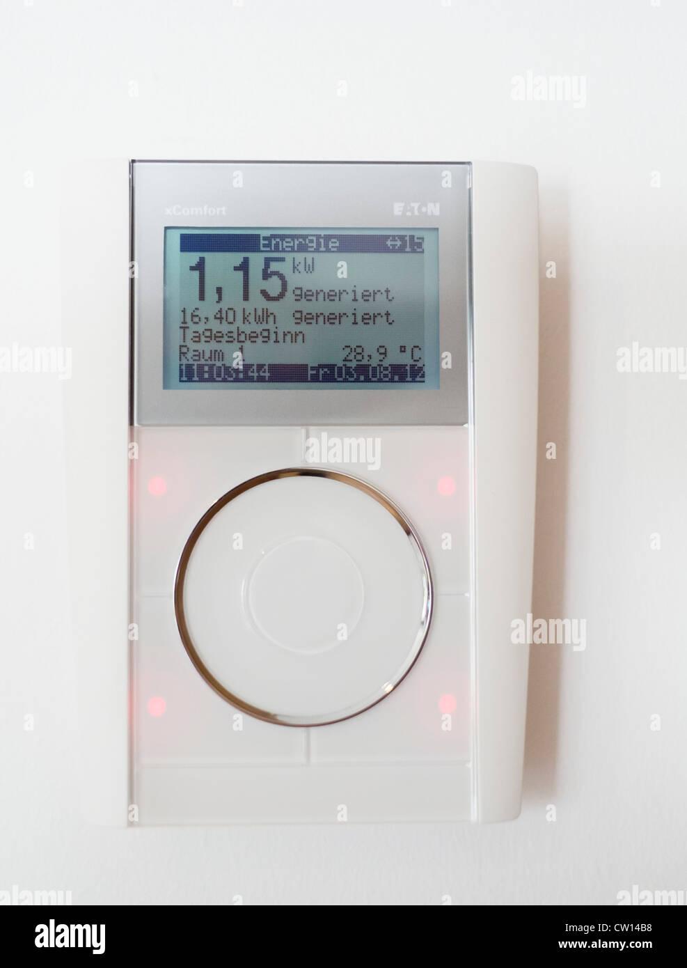 Termostato de pared y energía que muestra la energía generada por los paneles solares de alta eficiencia Imagen De Stock