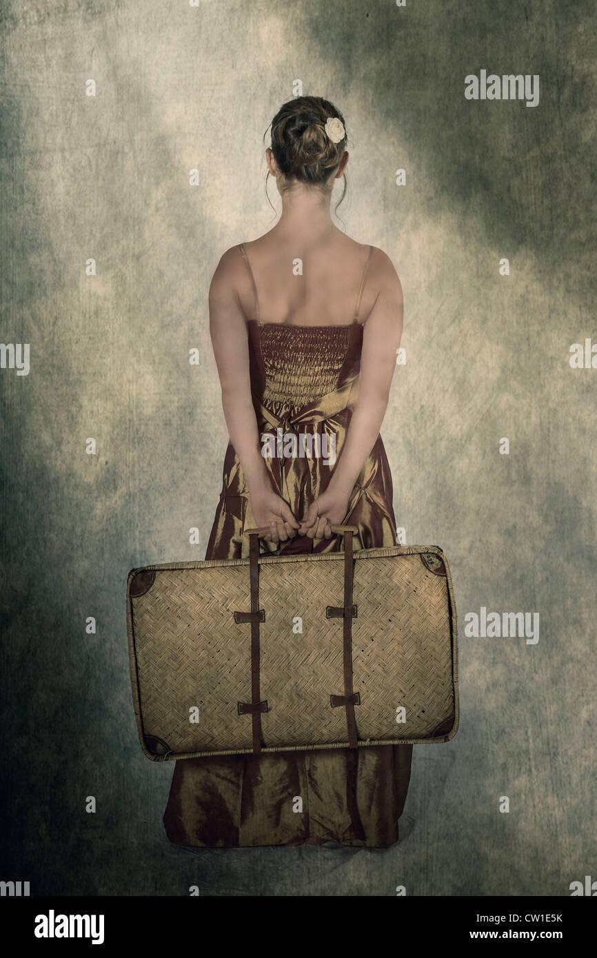 Una mujer en un período vestido sosteniendo una pequeña, vieja maleta detrás de su espalda Imagen De Stock