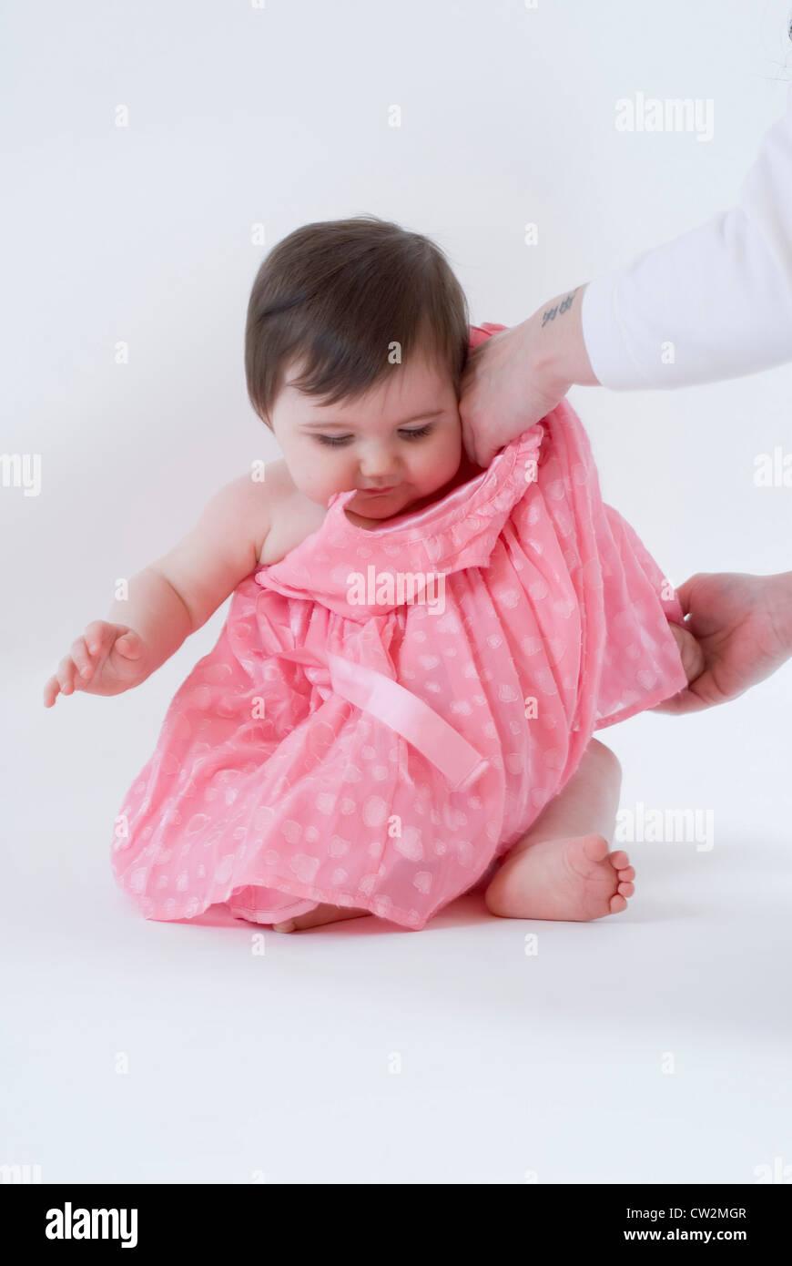 Cerca de Niña está vestida preguntando a sus volantes en color rosa ...