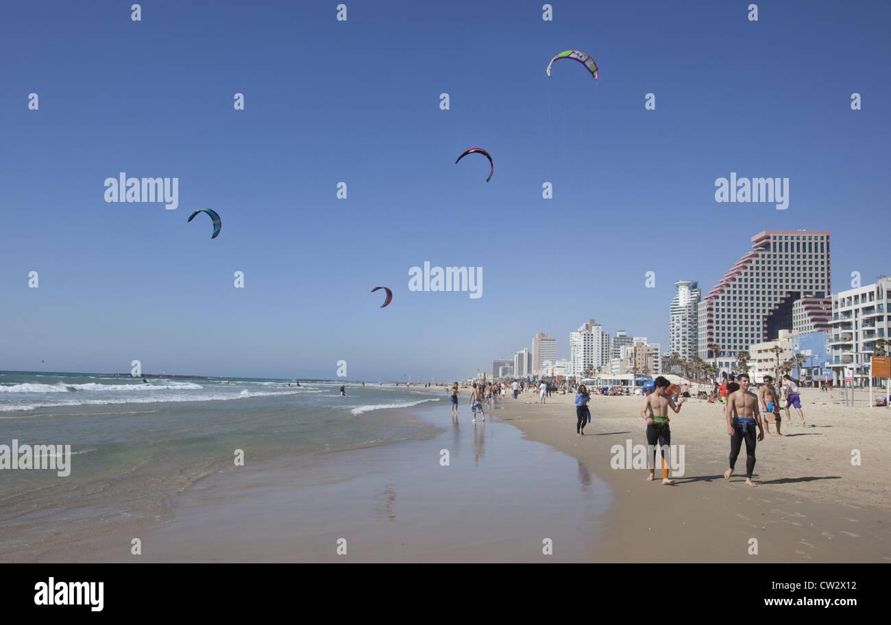 Los adultos jóvenes el enfriamiento después una corrida con cometas y kite-surf en el fondo, Tel Aviv, Imagen De Stock