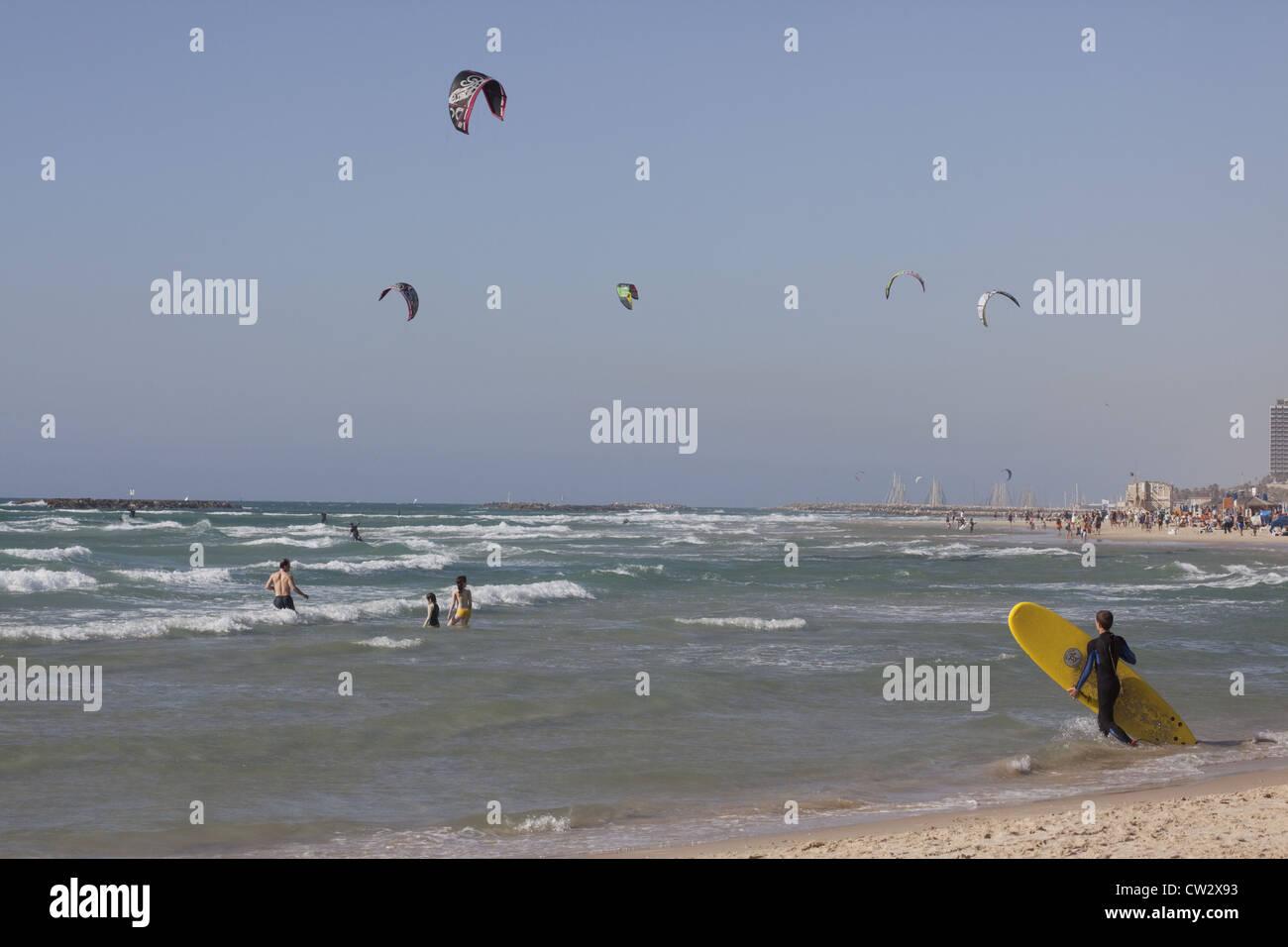 Surfista entrando en el agua con kite-surfers y bañistas en el fondo, Tel Aviv, Israel Imagen De Stock