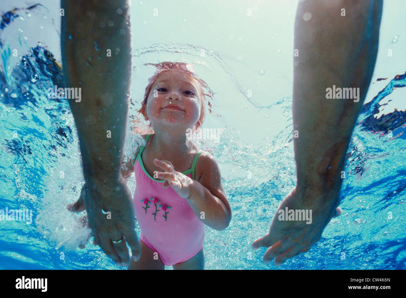 Close-up de manos del padre llegando a su hija bajo el agua Imagen De Stock