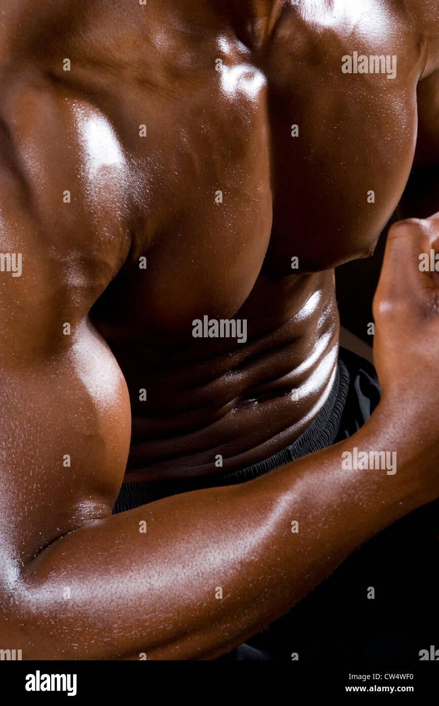 Sección media de un hombre joven flexionando los músculos en el gimnasio. Imagen De Stock