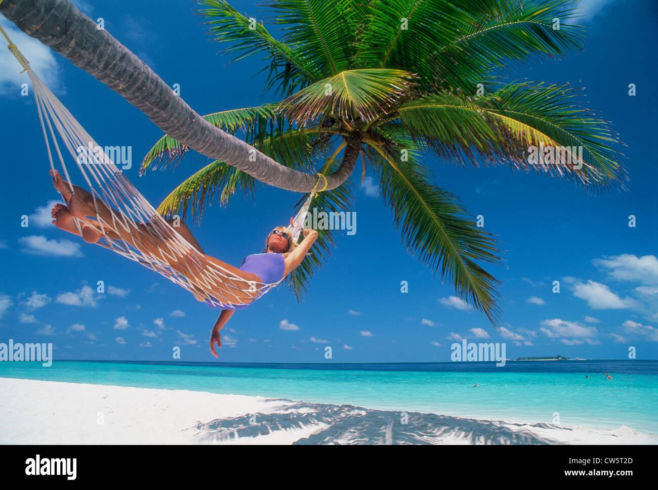 Mujer en hamaca bajo palmeras en un idílico entorno de vacaciones Foto de stock
