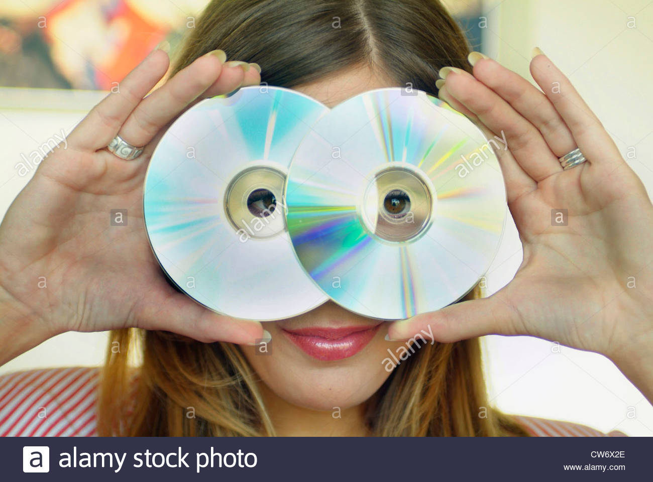 Hermosa mujer joven con pelo largo, mirando a través de dos CDs Imagen De Stock