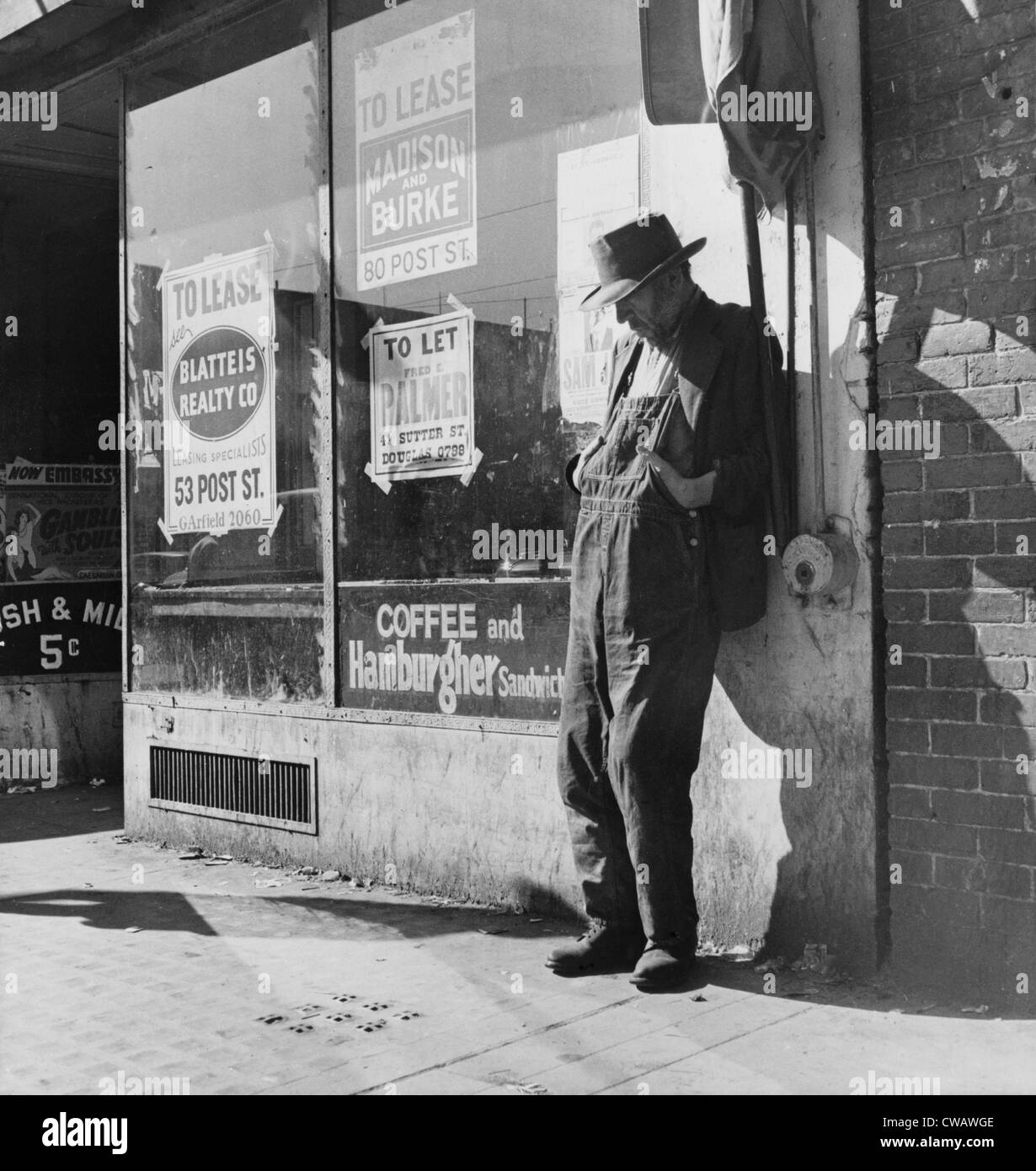 Hombre solitario en monos del agricultor, en San Francisco's Skid Row en Howard Street. Ruinas de granjeros del Foto de stock