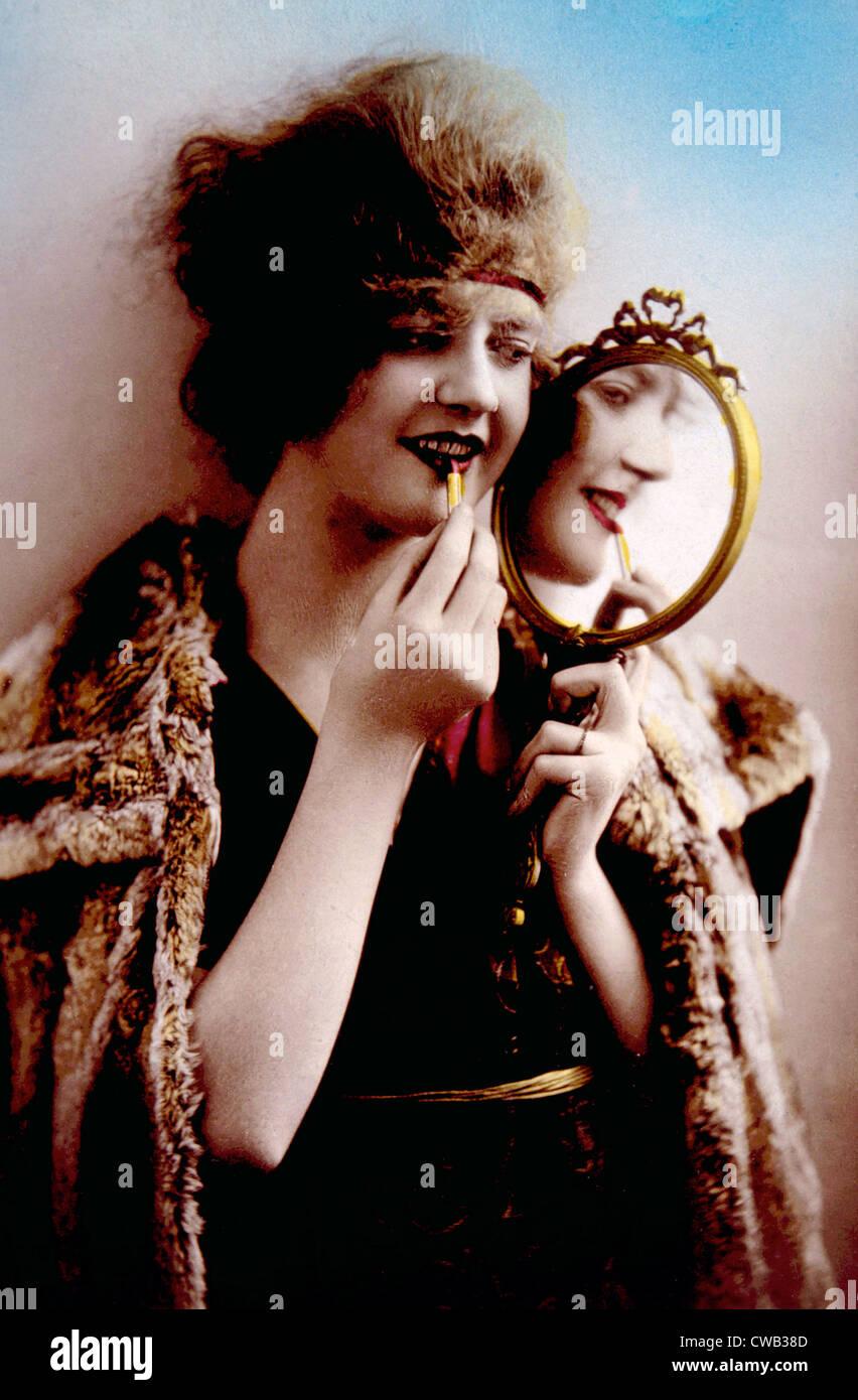 Las mujeres ocupan el espejo mientras aplico maquillaje, circa. 1900. Imagen De Stock