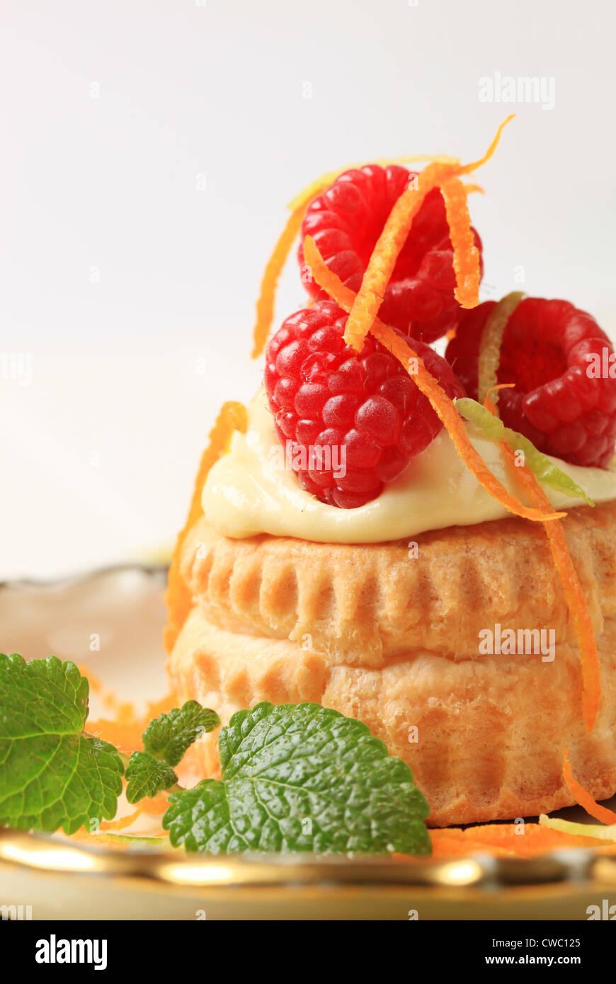 Shell de hojaldre rellenos de crema cubierto con frambuesas. Imagen De Stock