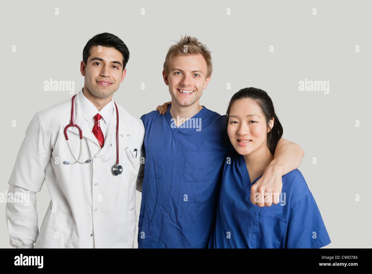 Retrato de simpático equipo médico parado sobre fondo gris Imagen De Stock