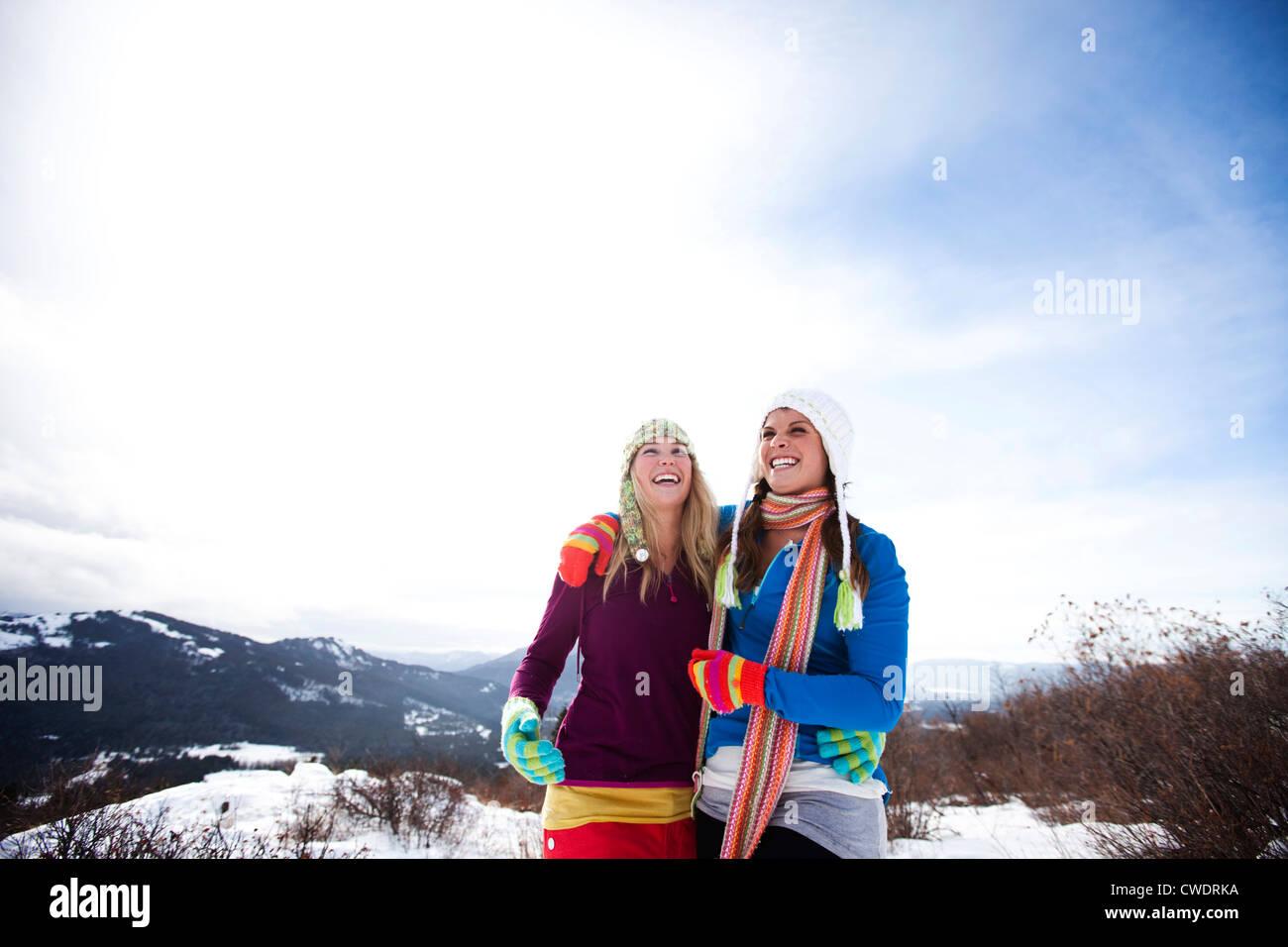 Dos mujeres jóvenes reír y sonreír mientras senderismo en la nieve en un hermoso día de invierno Imagen De Stock