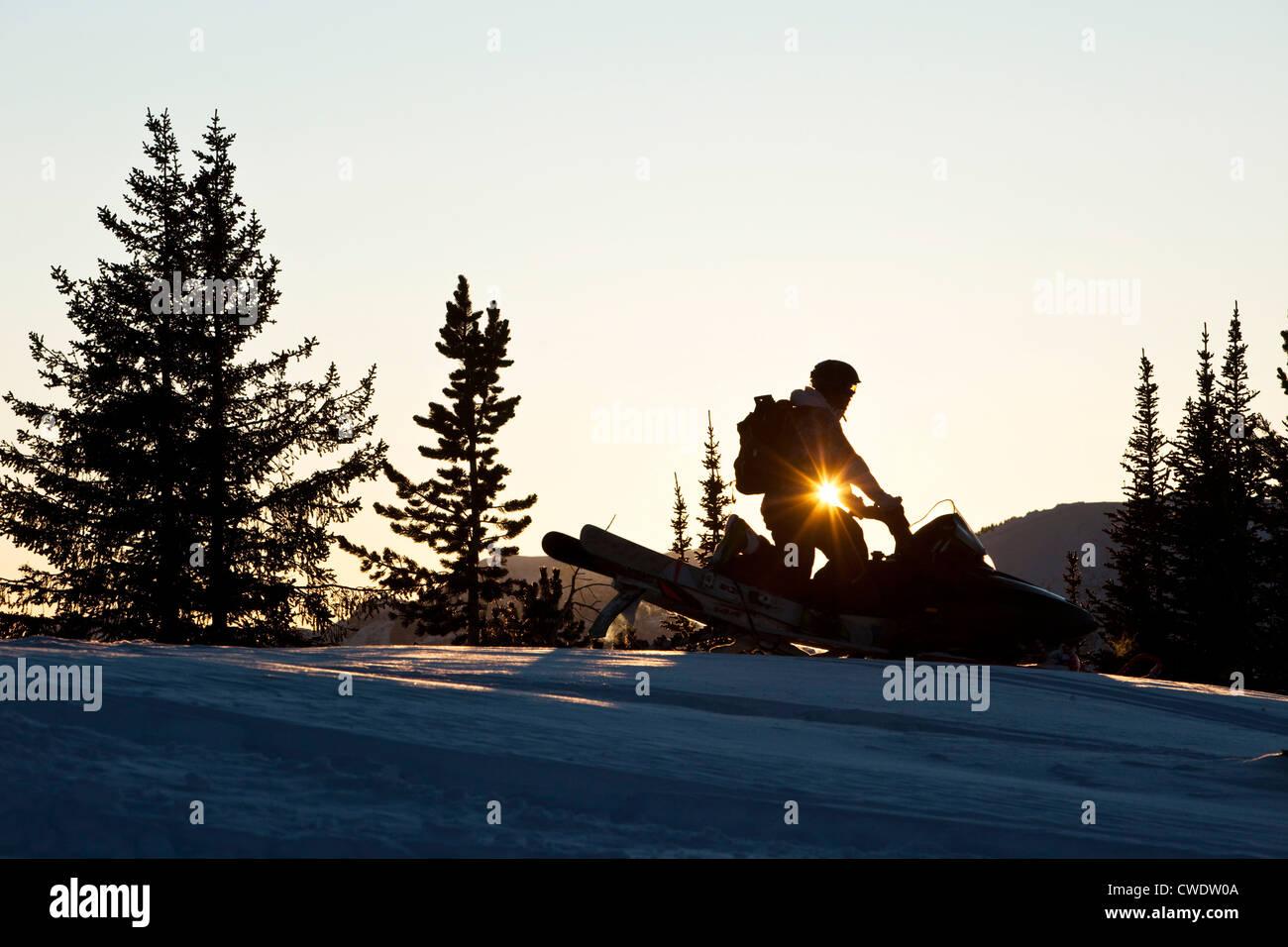 Un joven atlético snowmobiling al atardecer en Montana. Foto de stock