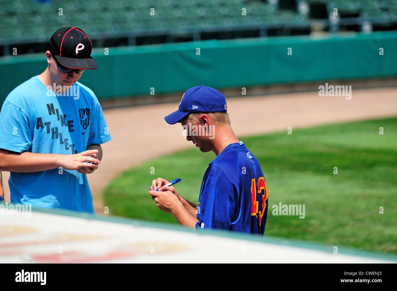 a09c4022478de Jugador de béisbol proporciona un autógrafo a un fan antes de iniciar un juego  de ligas