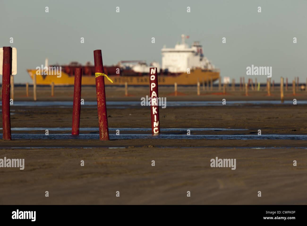 No hay señal de estacionamiento mano pintada en la pole con el buque de carga en el fondo que parece estar Imagen De Stock
