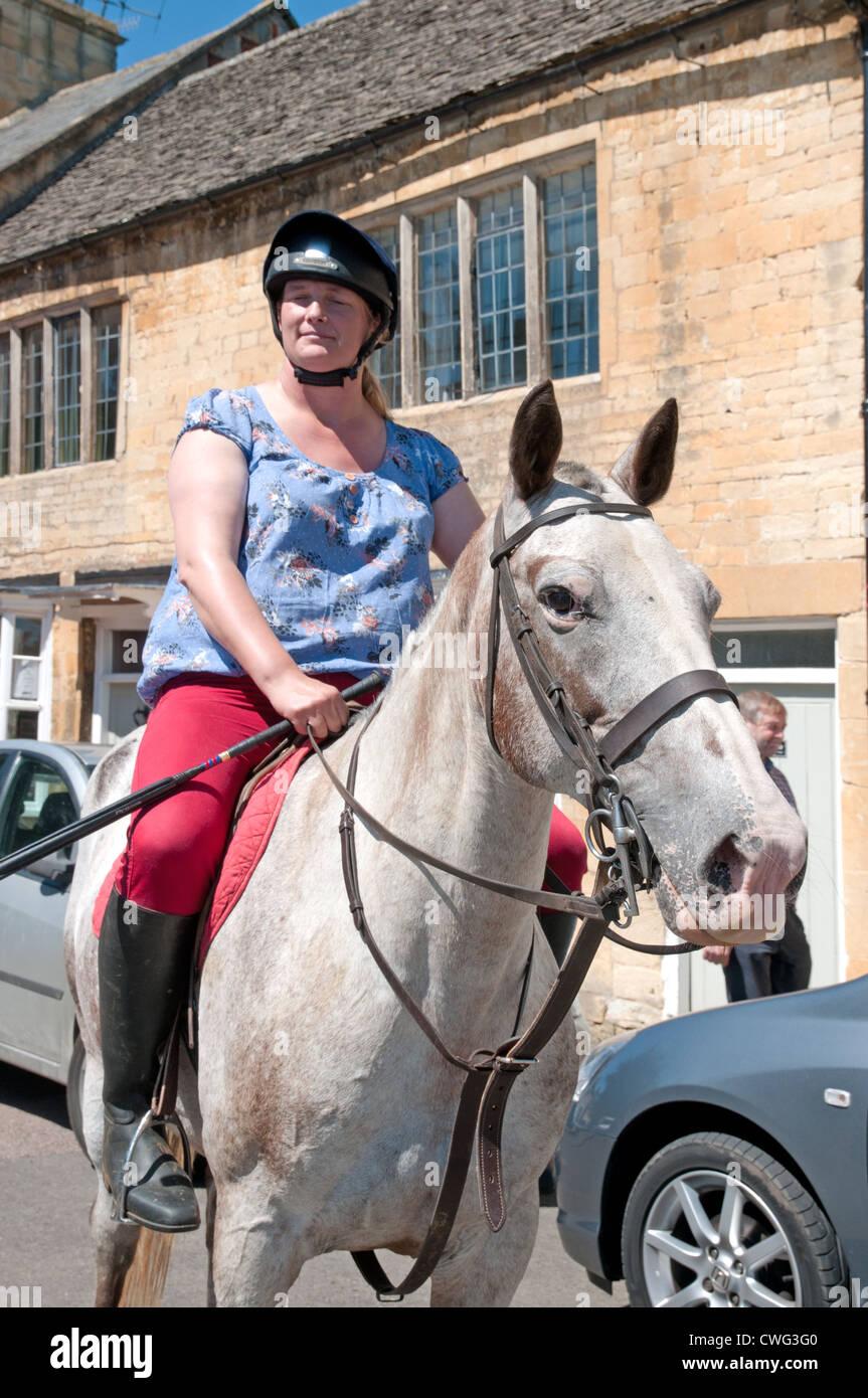 Señora montando a caballo en la parte inferior de la calle alta de Chipping Campden Gloucestershire Inglaterra Imagen De Stock