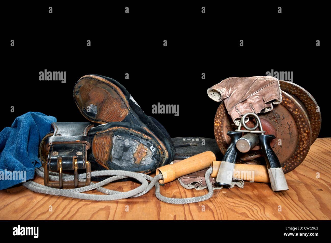 Una colección de viejos aparatos de ejercicios incluyendo asideros, dumbell, saltar la cuerda y viejo, roto Imagen De Stock