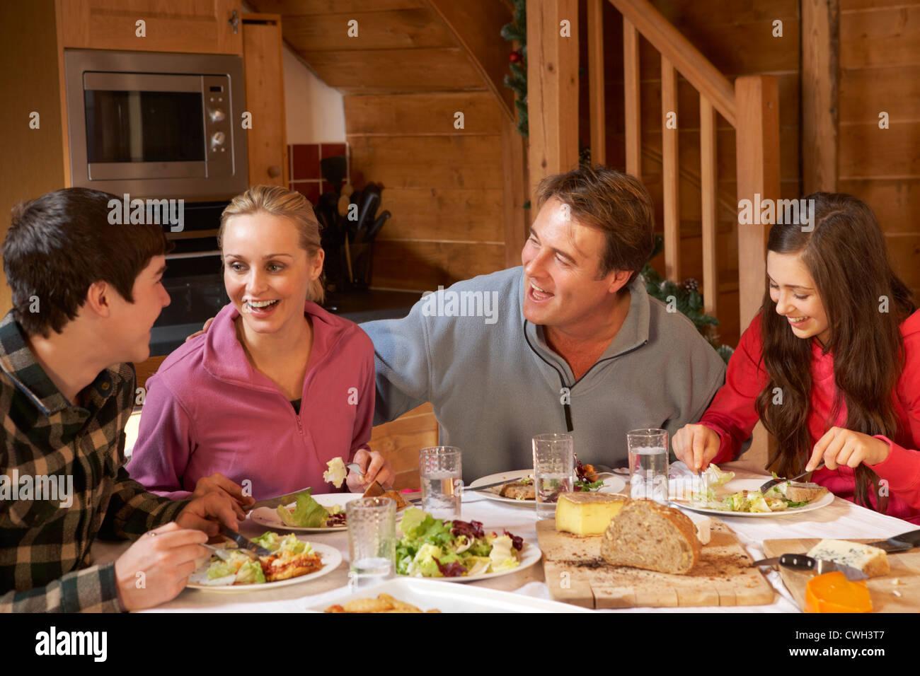 Familia adolescentes disfrutando de comida en chalet alpino juntos Imagen De Stock