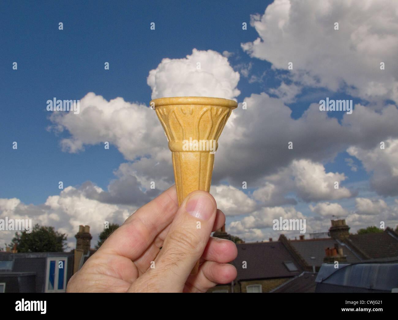 Una mano sujetando un cucurucho de helado con la nube detrás mirando como es helado Imagen De Stock
