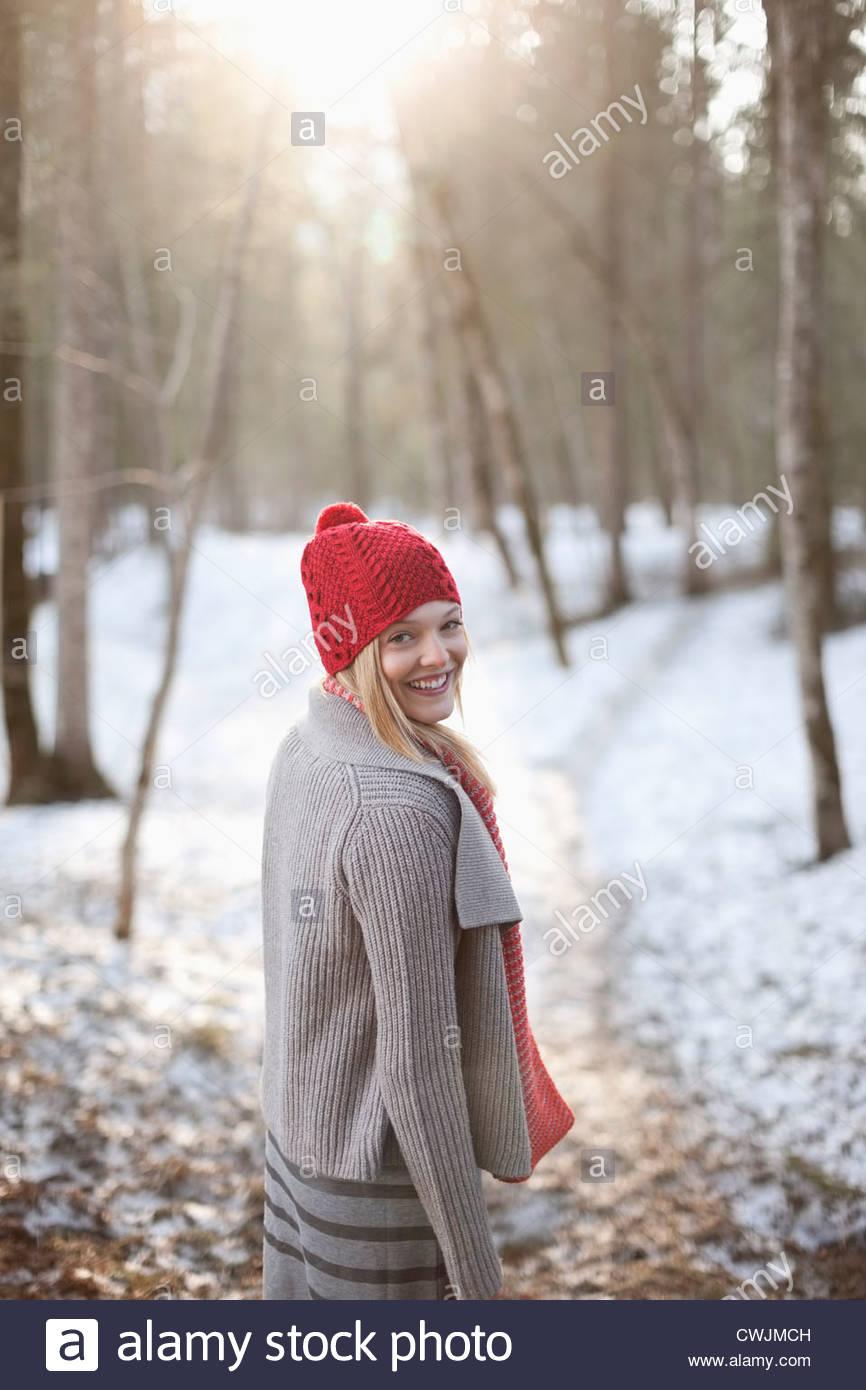 Retrato de mujer sonriente caminando en el bosque cubierto de nieve Imagen De Stock