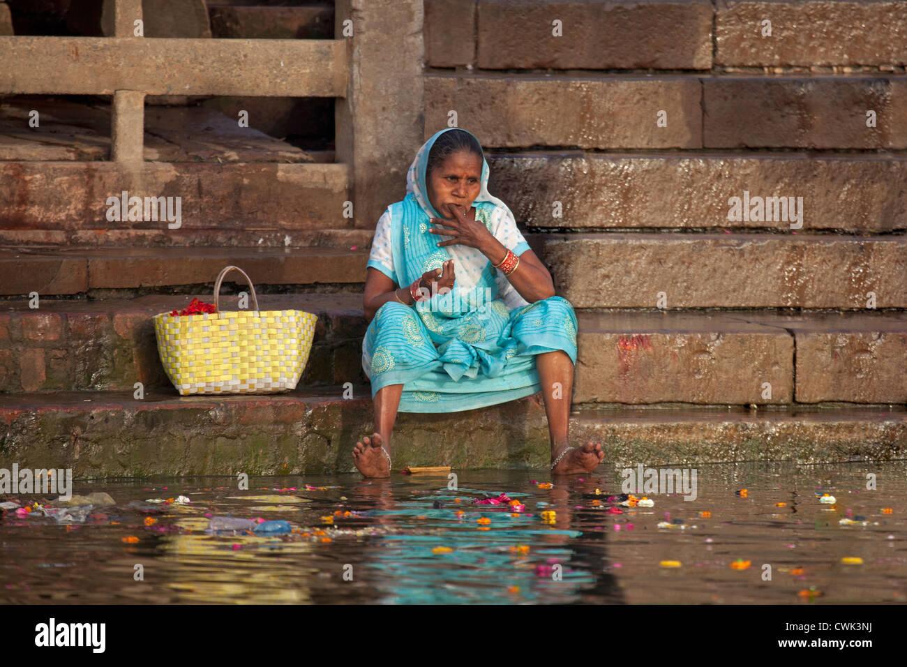 Mujer india antigua lavarse los dientes con el dedo sucio en el agua contaminada del río Ganges en Varanasi, Imagen De Stock