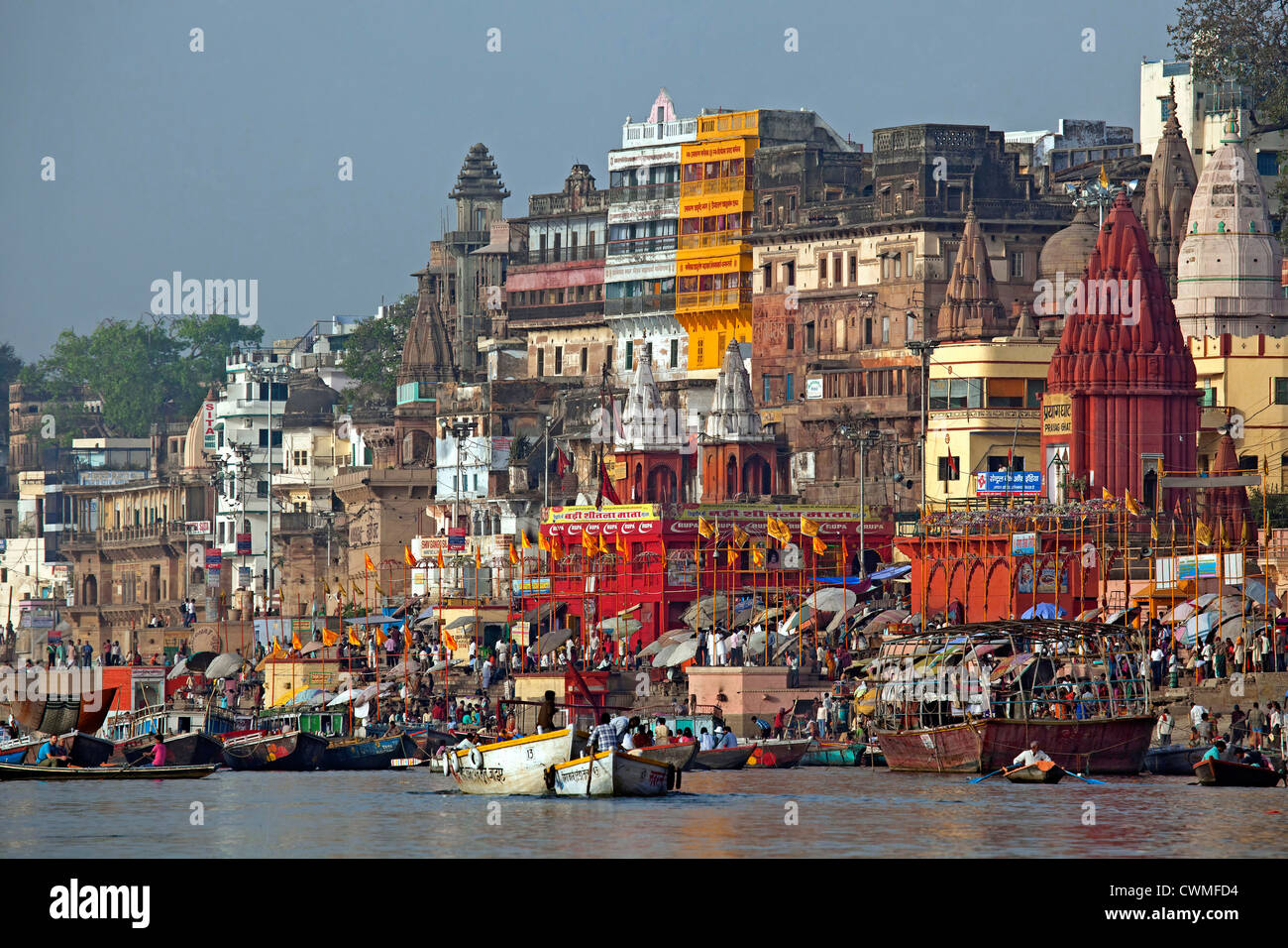 Peregrinos que visitan la ciudad santa y coloridas barcas de remo en el río Ganges en Varanasi, Uttar Pradesh, Imagen De Stock