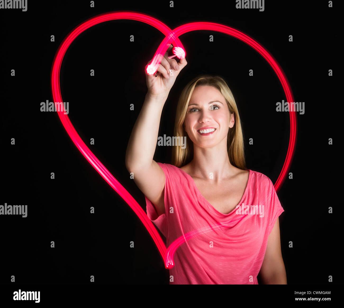 Mujer sacando corazón sobre fondo negro Foto de stock