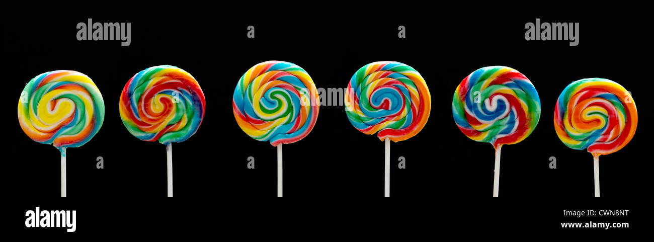 Whirly pops multicolor lollipops contra fondo negro. Panorámicas Imagen De Stock