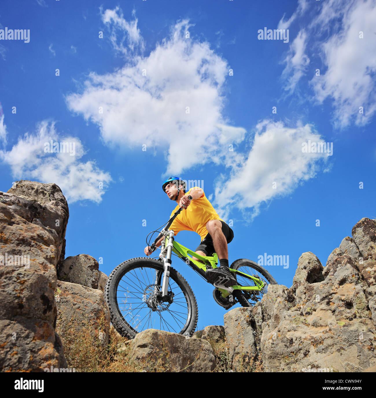 Una persona montando una bicicleta de montaña en un día soleado, bajo ángulo de visión Imagen De Stock