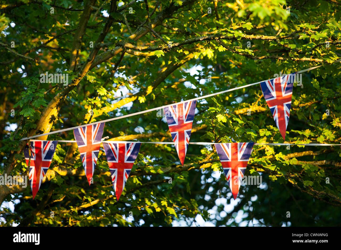 Bandera Union Jack bunting en fiesta en la calle para celebrar el Queen's Diamond Jubilee en Swinbrook en Cotswolds, Imagen De Stock