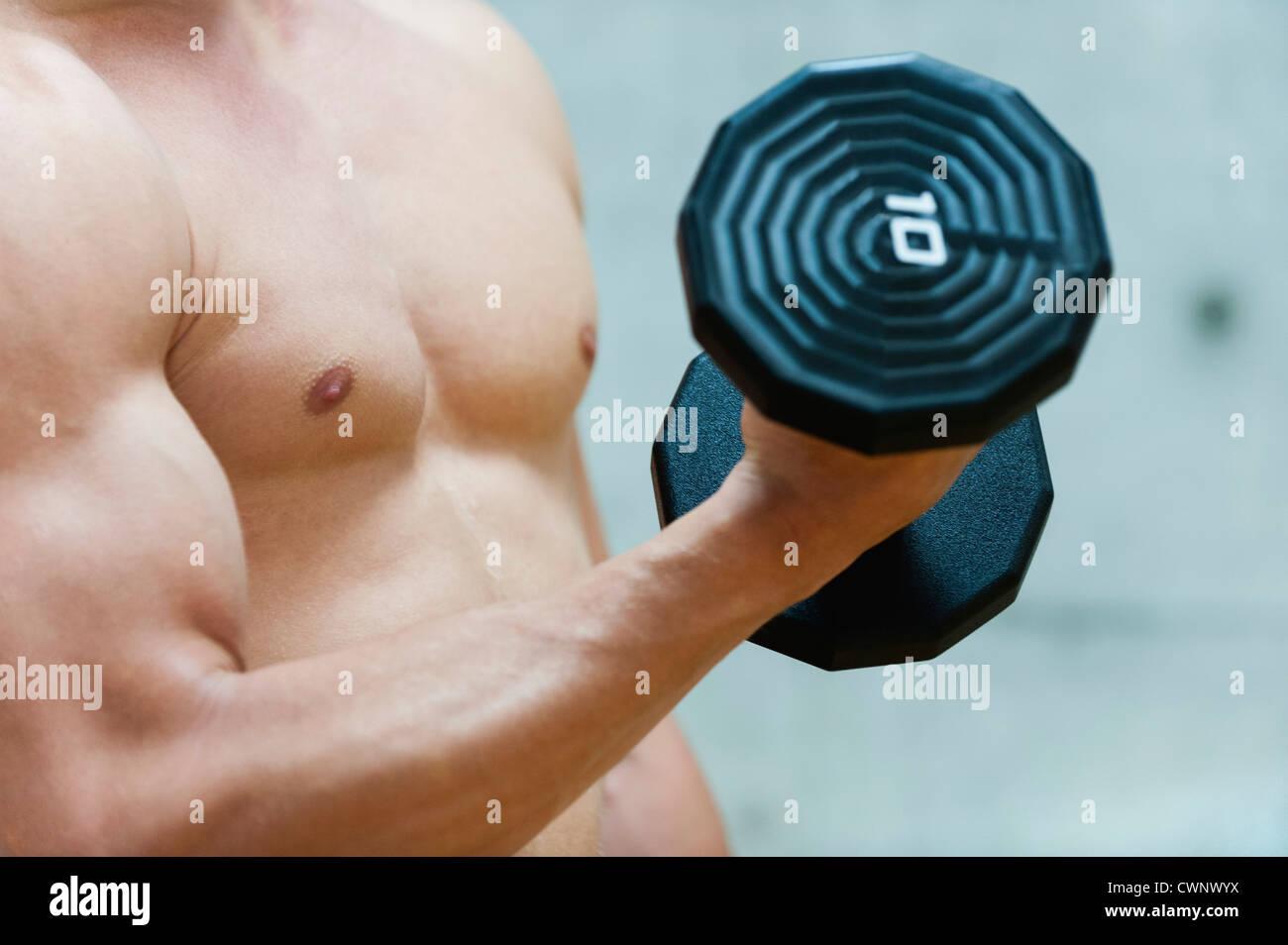 Hombre haciendo curl bíceps con pesa, sección intermedia Imagen De Stock