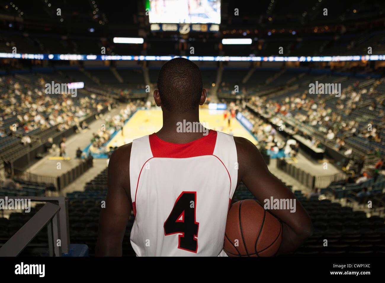El jugador de baloncesto mirando hacia abajo en el estadio, vista trasera Imagen De Stock