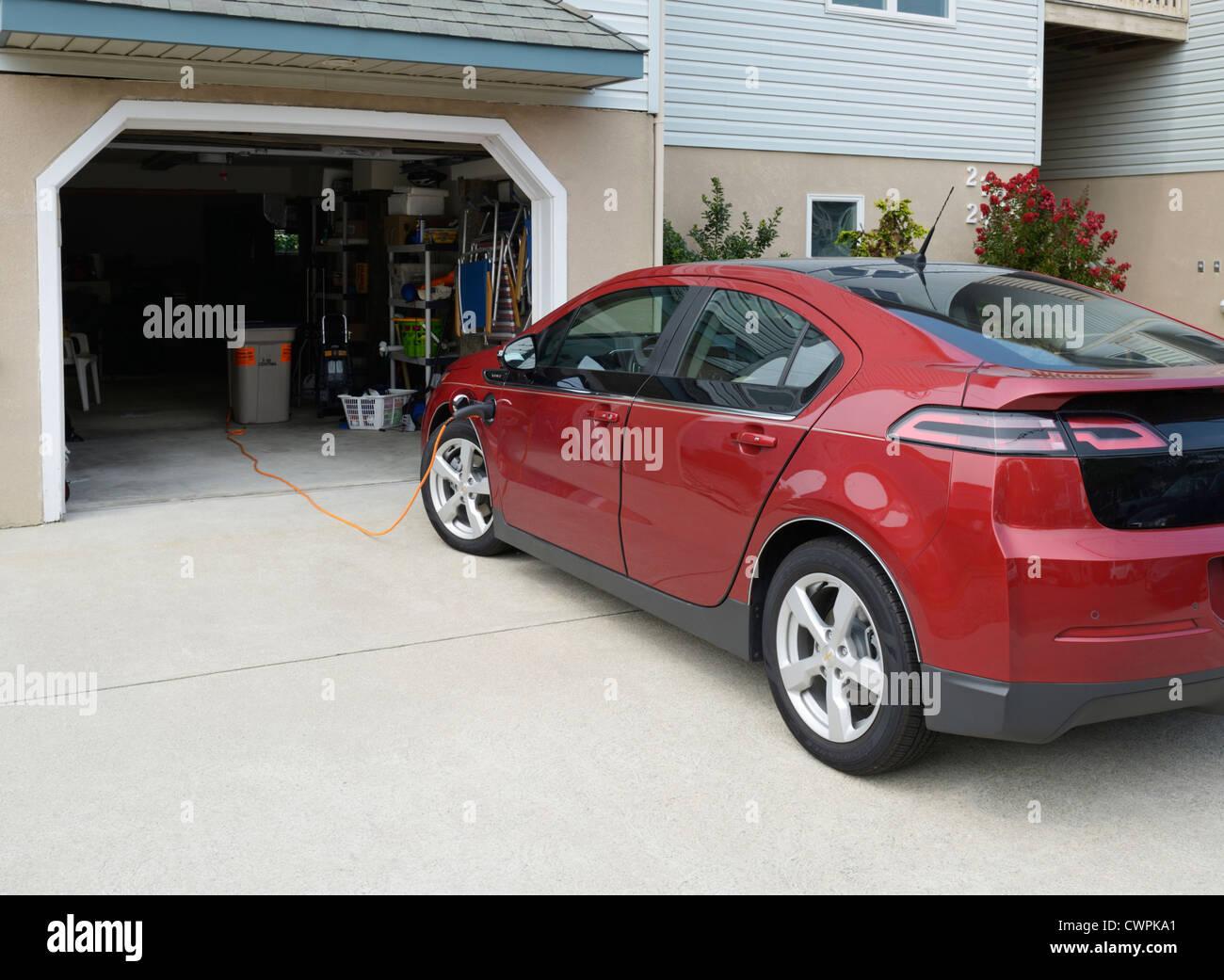 El Chevrolet Volt, el coche eléctrico, la recarga en una casa suburbana Imagen De Stock