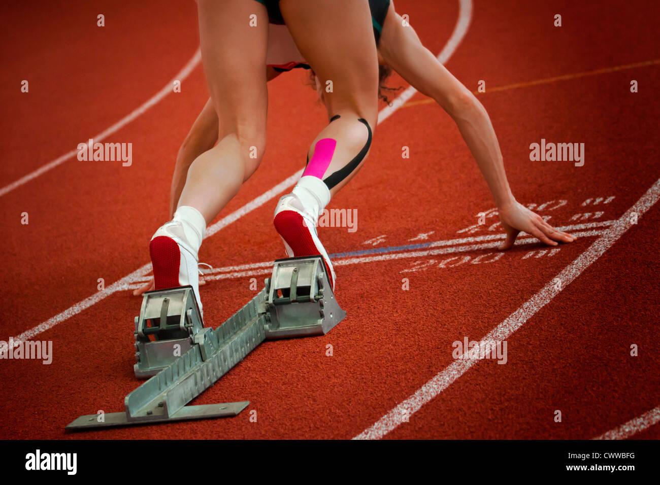 Distancia corta hembra runner en gravedad curva de pendiente está en posición de arranque Imagen De Stock