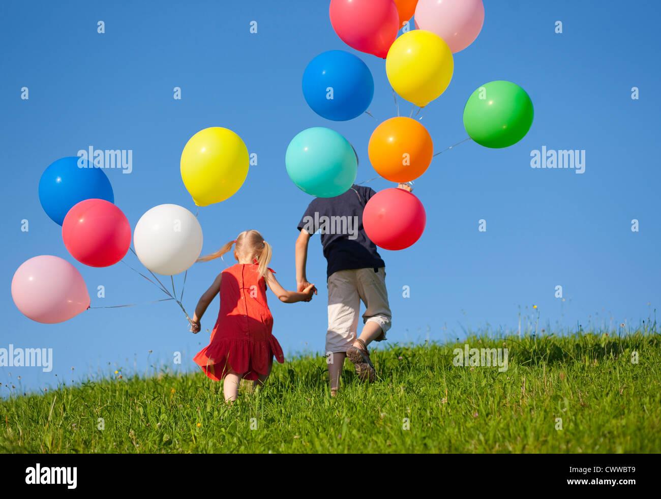 Los niños con globos de colores en la hierba Imagen De Stock