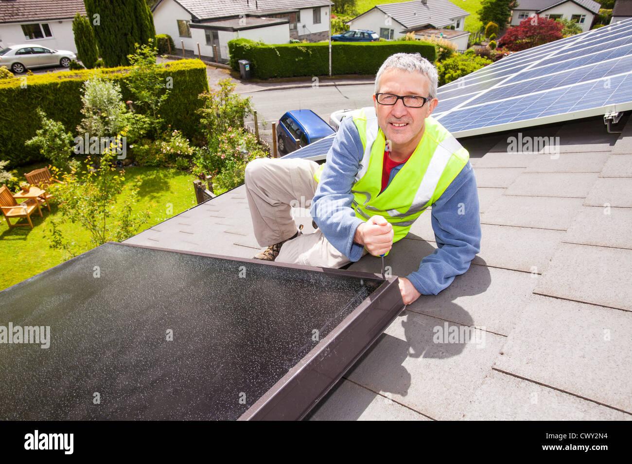 Un obrero colocación de paneles solares térmicos para calentar el agua, a una casa de techo en Ambleside, Imagen De Stock