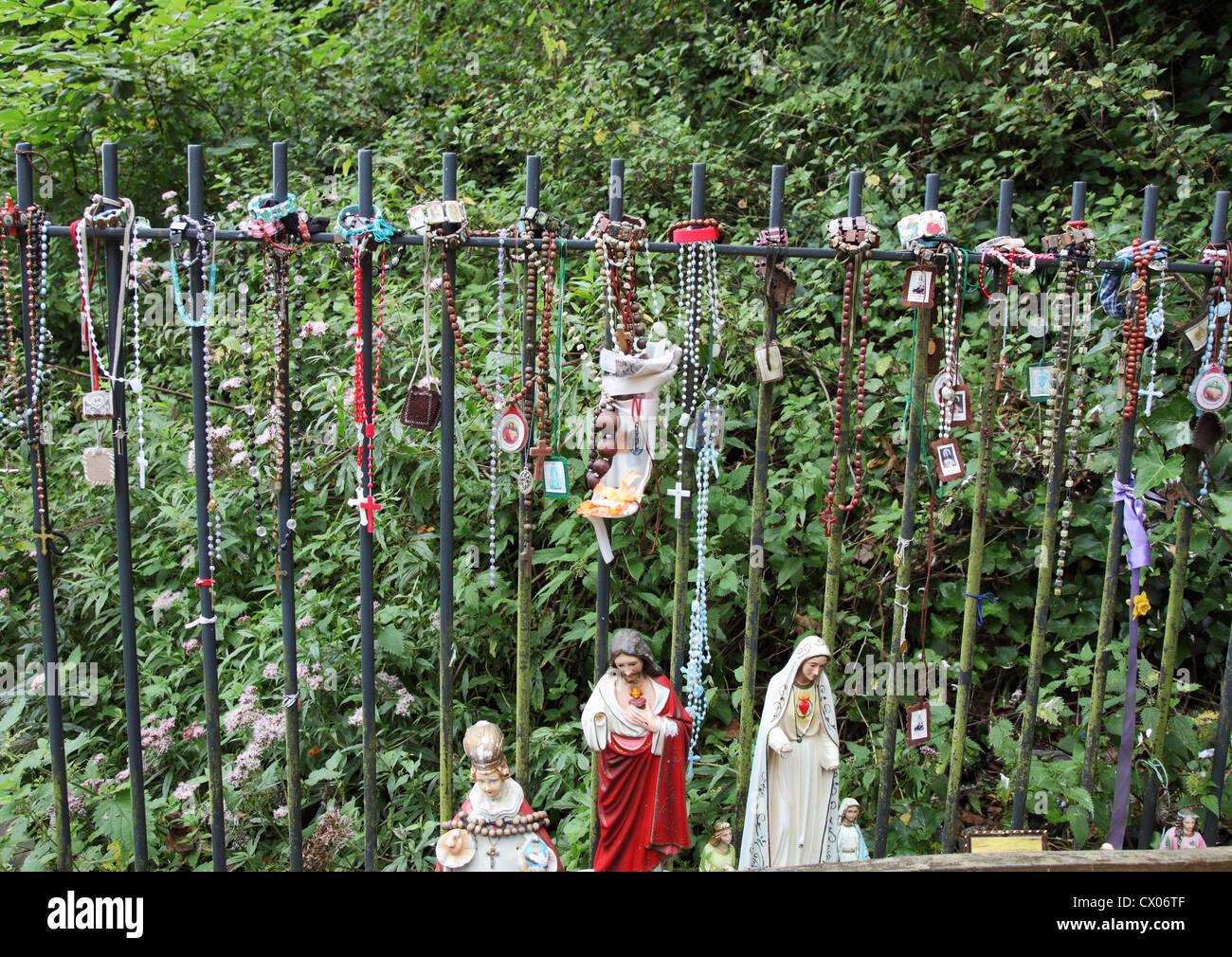 Rosarios y otros artículos religiosos forman un pequeño santuario en St Winefride bien, Holywell, North Imagen De Stock