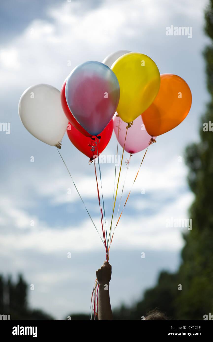 Persona sosteniendo multicolores globos de helio Imagen De Stock