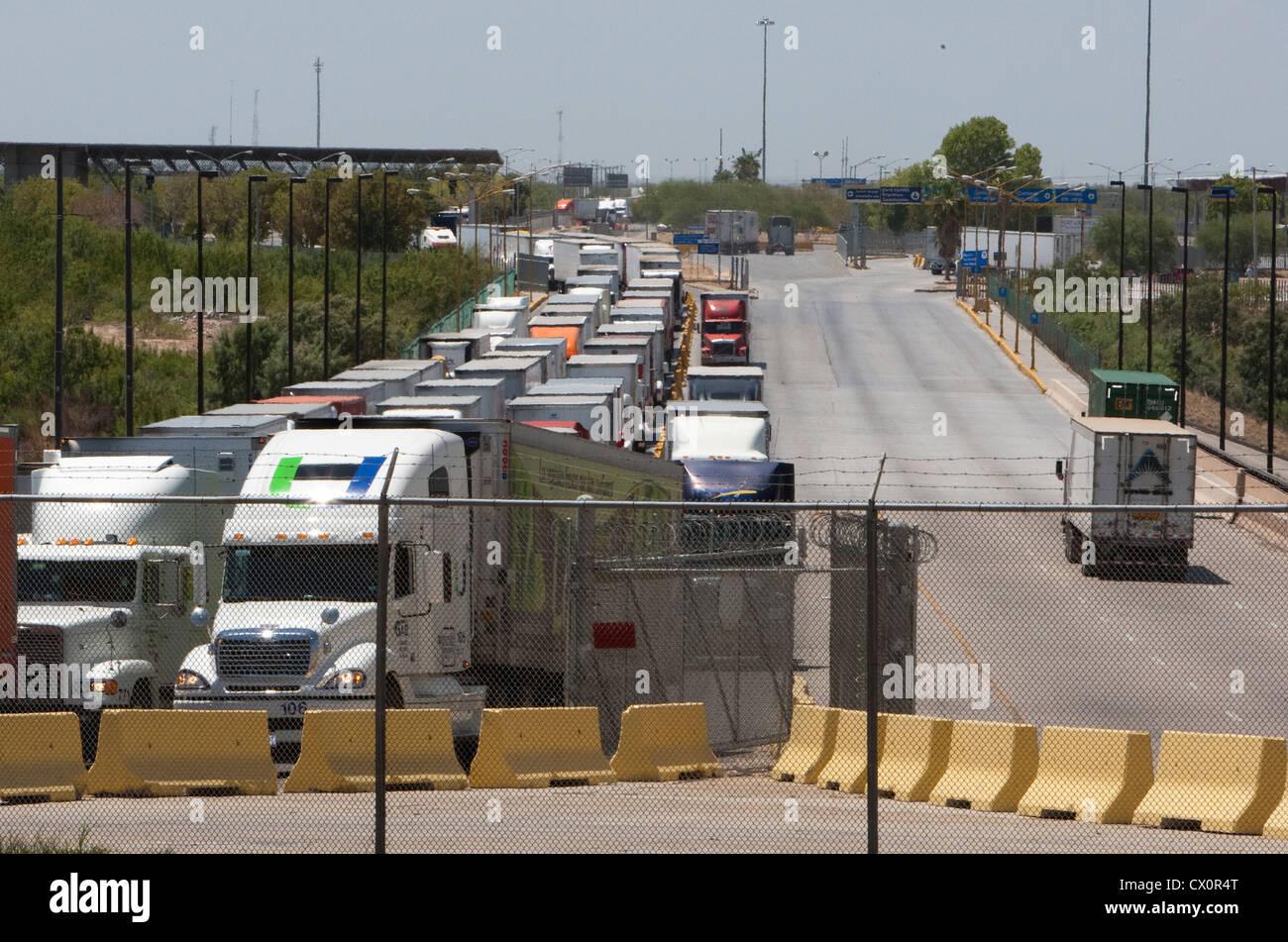 Larga fila de camiones que esperan para entrar a los Estados Unidos procedente de México en el comercio mundial de puente internacional en Laredo, Texas Foto de stock