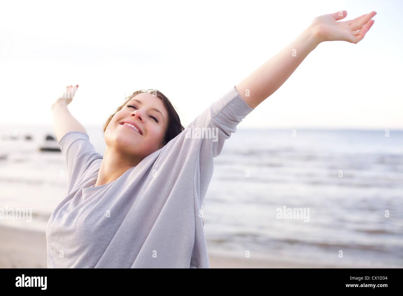 Mujer estirando sus brazos para disfrutar del aire fresco del mar Imagen De Stock