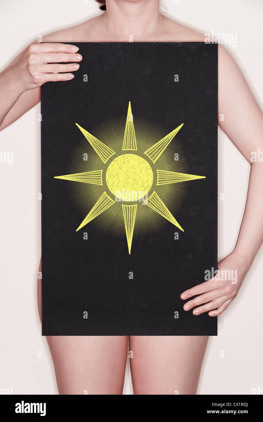 Mujer sosteniendo una pizarra de tiza con una ilustración de un sol - concepto imagen Imagen De Stock